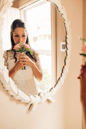 Bride before the wedding looking at smelling her roses wedding bouquet in the mirror nervously. Important day. Wedding and marry concept. Banque d'images