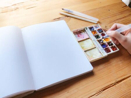 Watercolor paint canva and brushes used to create new paintings. Hand holding a brush. Starting a bullet journal in a dot notebook. New beginnings. Art and creativity concept.