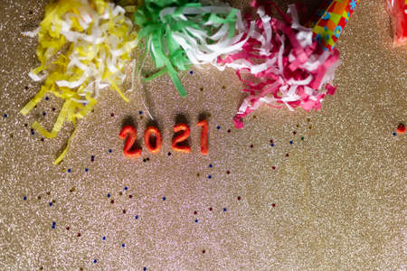 Party trumpets with confetti celebrating new year 2021. Colorful party horns on glitter gold background. Stock Photo