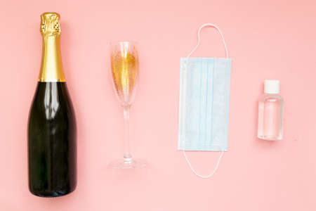 Bottle of champagne face mask hand sanitizing gel and glasses with gold glitter on pink background. Party decor. Christmas, birthday or wedding concept. Flat lay. Festive, drink. New year 2021 celebration.