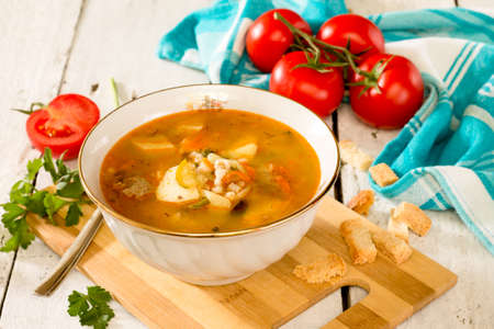 ukranian: Solyanka, meat and pickle soup on in a white ceramic bowl on a white wooden background. Traditional Russian and Ukranian soup Stock Photo