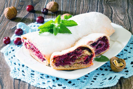 Delicious homemade cherry strudel with walnuts on a wooden background