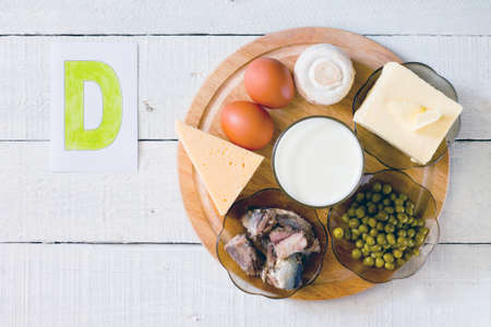 Voedingsmiddelen met vitamine D: kaas, eieren, champignons, melk, boter, erwten in blik in olie
