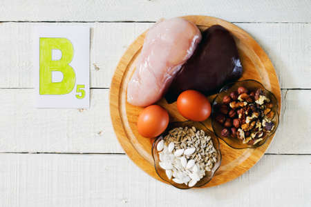 vitamins: Foods that contain vitamin B 5: walnuts, hazelnuts, sunflower seeds, pumpkin seeds, meat, liver, eggs Stock Photo