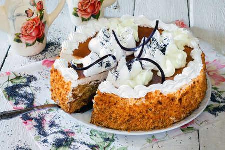 honey cake: Honey cake with whipped cream and caramel on a white wooden background. Stock Photo