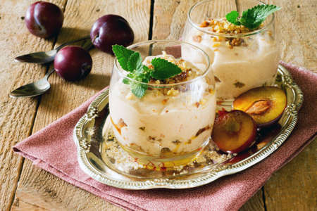 plum pudding: Dessert con panna montata, arrostito avena noci, prugne e noci in bicchieri di vetro su un tavolo di legno