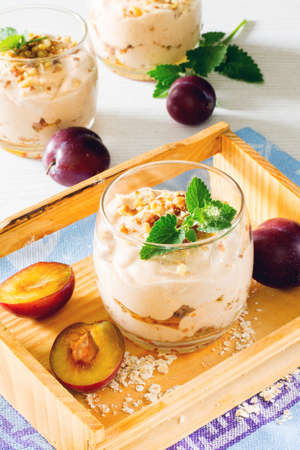 plum pudding: Dessert with whipped cream, roasted nuts oatmeal, prunes and walnuts in glass glasses on a wooden table