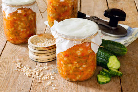 pearl barley: preserves pearl barley, cucumber, pickle in the bank on a wooden background