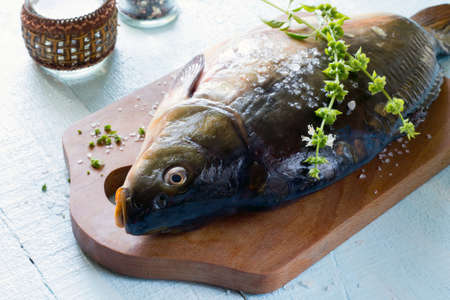 tench: Raw fish (tenchе) with basil on a wooden table Stock Photo