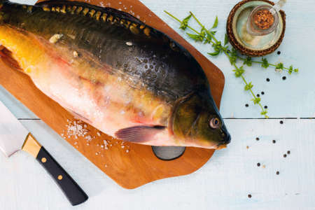 tench: Raw fish (tenchе) with basil on a wooden table, top view Stock Photo
