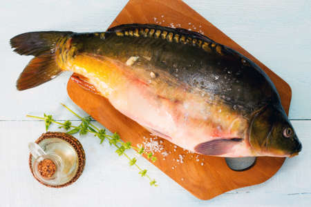 tench: Raw fish (tenchе) on a wooden cutting board, top view