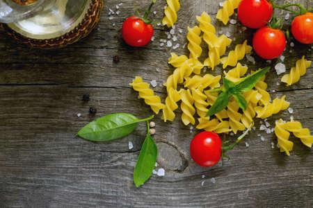 sunflower oil: Pasta, fresh cherry tomatoes and sunflower oil on a dark gray background
