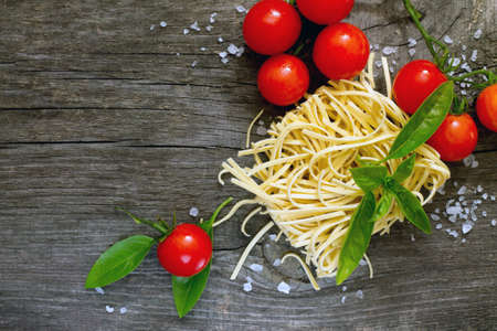 egg noodles: Egg noodles, basil and fresh cherry tomatoes on a dark gray background Stock Photo
