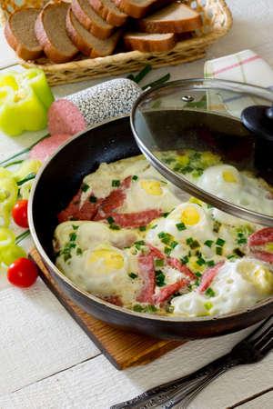 huevos revueltos: Los huevos revueltos fritos con rodajas de salchicha de desayuno delicioso