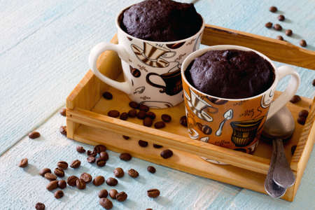 cake: Quick chocolate coffee cake in a cup on a wooden table