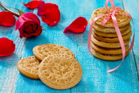 Koekjes met honing en kaneel op Valentijnsdag en een rode roos Stockfoto