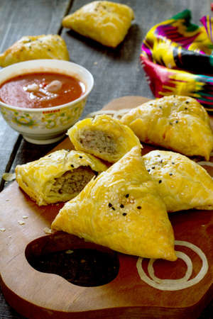 uzbek: Traditional oriental food samosa, meat pies on a wooden table Stock Photo