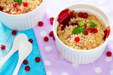 to crumble: Dessert with red currant crumble, selective focus.