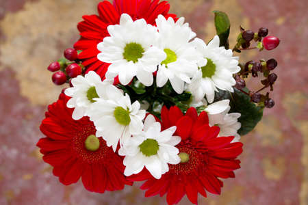home accents: Bouquet of flowers with a red flower gerbera daisy on a wooden vintage background, top view. Stock Photo