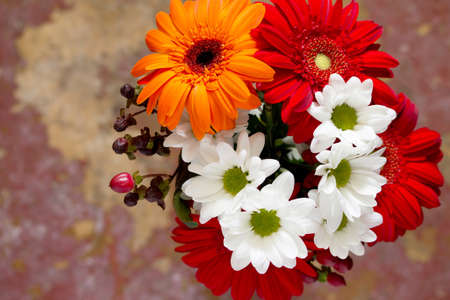 home accent: Bouquet of flowers with a red flower gerbera daisy on a wooden vintage background, top view. Stock Photo