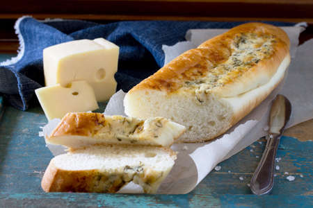 long loaf: Bread long loaf baguette with cheese and herbs on a vintage wooden blue background.