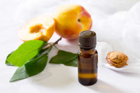Cosmetic oil from the seeds of peach in a glass bottle on a gray stone background.