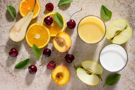 desirable: Assortment of fruits and berries for making milkshakes on the stone background. Fresh organic ingredients. Desirable and health food concept or detox diet.