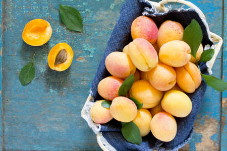 foodstuff: Harvest fresh ripe peaches in a wicker basket on old wooden table, top view. Stock Photo