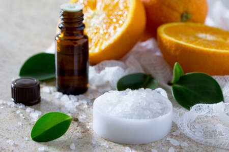 Bottle of orange essential oil aromatherapy and salt on brown stone background. Spa Orange.