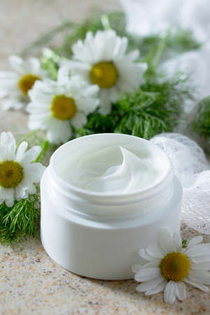 salon background: Face cream with chamomile on a brown stone background - beauty salon.