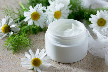 Face cream with chamomile on a brown stone background - beauty salon.