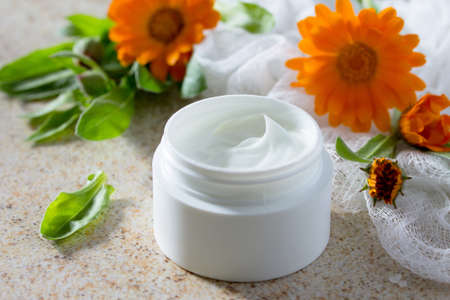 salon background: Face Cream marigold on brown stone background - beauty salon.