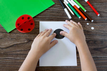 art and craft: Child glues paper details on a postcard. The child makes a postcard with ladybird. Glue, paper, scissors on a wooden table. Childrens art project, a craft for children.