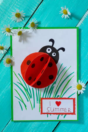 Colorful paper card with ladybug, grass, and the words I love summer, camomile on a blue wooden background. School and kindergarten paper crafts. Summer fun background. 免版税图像