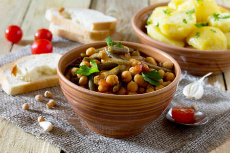 Vegetarian vegetable stew with chickpeas and green beans on a rustic background, healthy eating, diet, vegetarian cuisine and the concept of cooking. Stock Photo