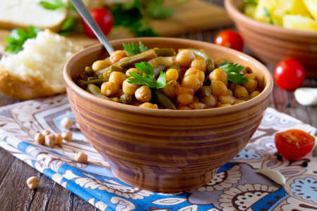Healthy eating, diet, vegetarian cuisine and cooking concept - stewed chickpeas with tomatoes, garlic and green beans. Boiled potatoes garnish.