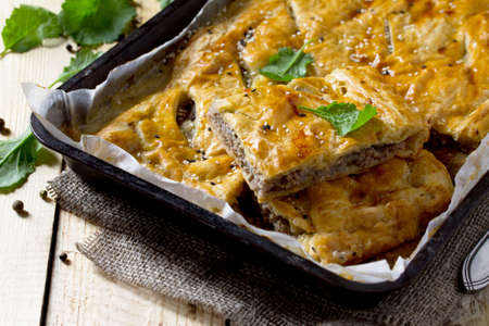 Pie with meat (minced meat and puff pastry) on the table in a rustic style.