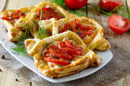 Cakes with red fish (salmon) and tomatoes on a table in a rustic style.