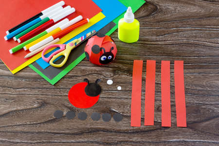 The child makes crafts out of paper ladybug. Glue, paper, scissors on a wooden table. Children's art project, a craft for children. 免版税图像