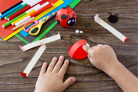 The child holds a piece of paper and glues the of the handicrafts. The child makes crafts out of paper ladybug. Glue, paper, scissors on a wooden table. Childrens art project, a craft for children.