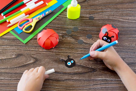 The child draws a piece of paper. The child makes crafts out of paper ladybug. Glue, paper, scissors on a wooden table. Children's art project, a craft for children.