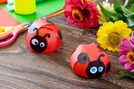 Colorful paper for children handmade odd job ladybug on a wooden table and the flowers. School and kindergarten paper crafts. Summer fun background. Stockfoto