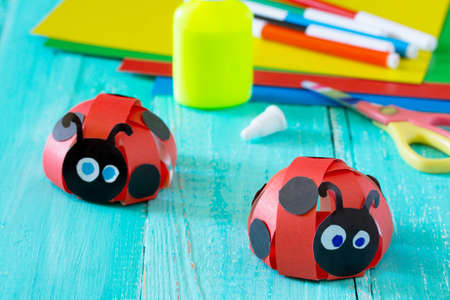 Colorful paper for children handmade odd job ladybug on a blue wooden background. School and kindergarten paper crafts. Summer fun background.