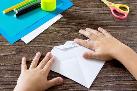 pegamento: El niño sostiene un cuadrado tira de papel y doblar la esquina. El niño hace artes de barco de papel. Pegamento, papel, tijeras en una mesa de madera. proyecto de arte para niños, un arte para los niños.