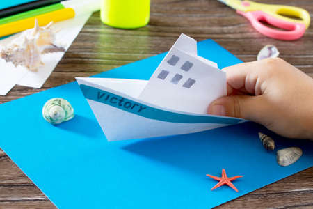 Crafts Paper Boat, origami. Glue, scissors, paper, starfish and seashells on a wooden table. Childrens art project, a craft for children. Stock Photo