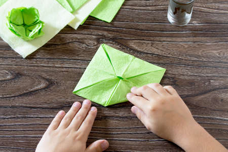 The child holds a paper square and fold it corner. The child makes crafts out of paper lily. Paper napkins on a wooden table. Childrens art project, a craft for children.