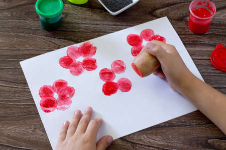 The child makes drawing on paper by using the print potatoes and fingers. Glue, paint, paper and potatoes on a wooden table. Children's art project, a craft for children.