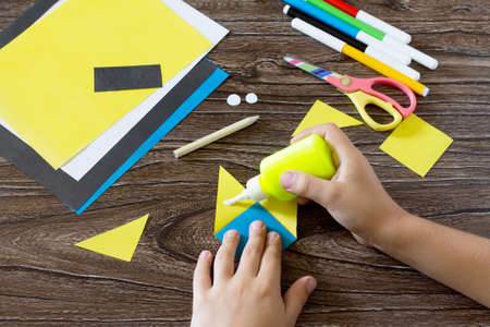 The child makes a book with a bookmark mignon. The child bonded items paper products. Glue, paper, scissors on a wooden table. Children's art project, a craft for children.