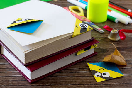 The child makes the book bookmark cartoon character mignon. Glue, scissors, paper and autumn leaves on a wooden table. Children's art project, a craft for children.