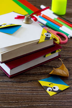 The child makes the book bookmark cartoon character mignon. Glue, scissors, paper and autumn leaves on a wooden table. Copy space. Childrens art project, a craft for children. Stock Photo